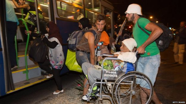 Migrants board buses in central Budapest {image source: bbc.com}