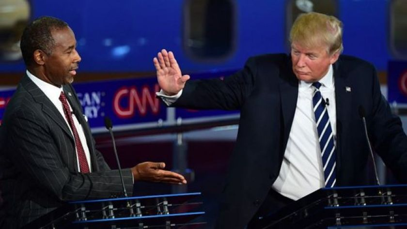 Donald Trump and Ben Carson slap hands at a presidential debate.