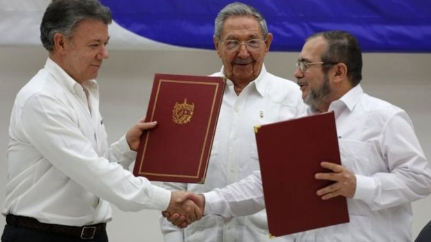 Colombian President Juan Manuel Santos, left, and Commander of Farc, Timoleon Jimenez, right, shake hands during a signing ceremony of a ceasefire and rebel disarmament deal, in Havana, Cuba.