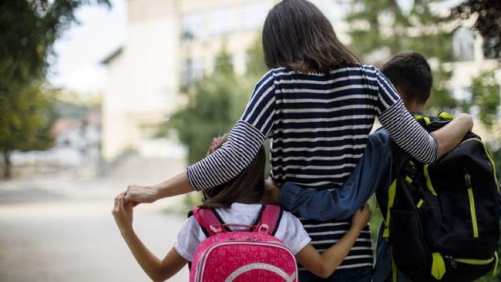 Madre lleva a niños a al escuela.
