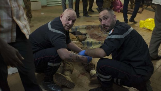 French gendarmes tend to wounded people in the surrounding of the hotel Splendide and the café Cappuccino during the attack on January 15, 2016.