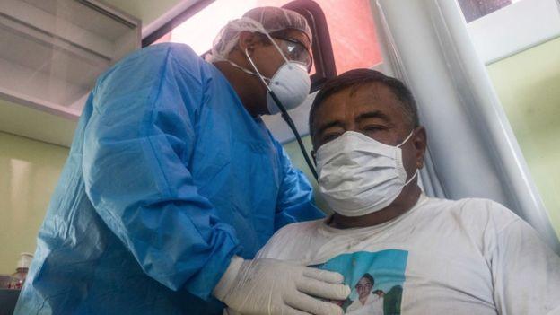 Un médico vistiendo equipo de protección personal atiende a un paciente en Perú.