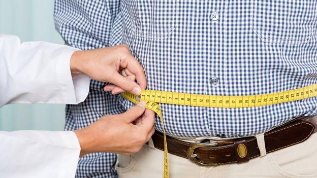 Doctor midiendo el sobrepeso de un hombre.