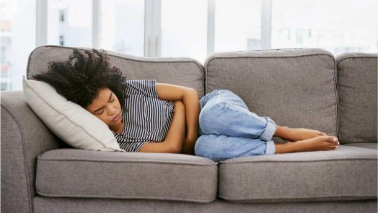 Mujer en el sofá con dolor abdominal.