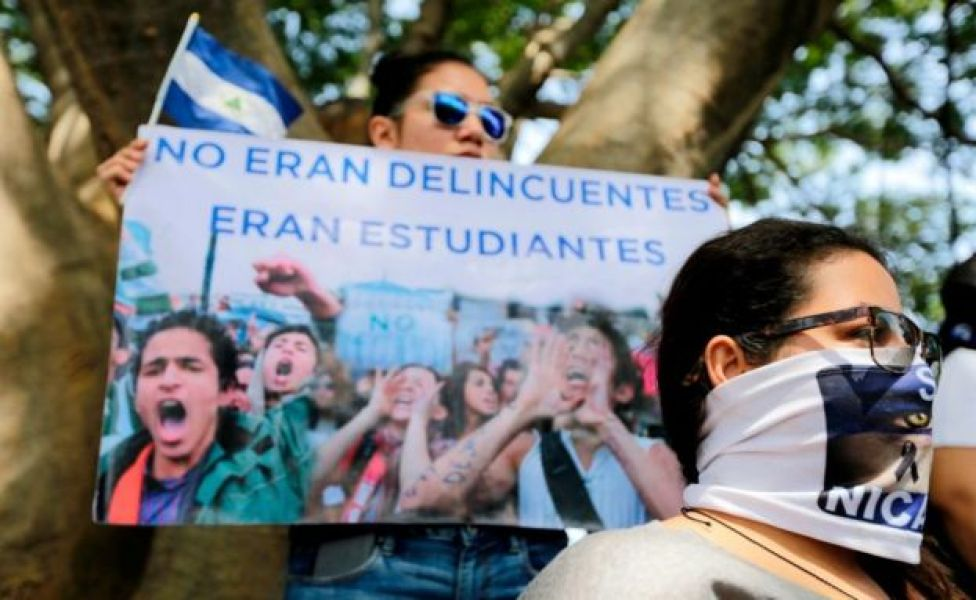 A woman holds a sign reading 'They were not criminals, they were students' in a protest in Nicaragua, July 2018