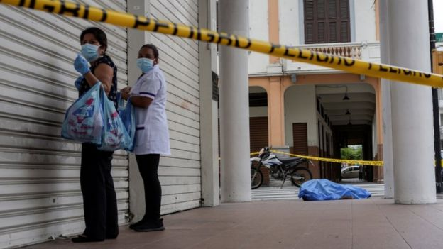 Mulheres passam por cadáver na rua
