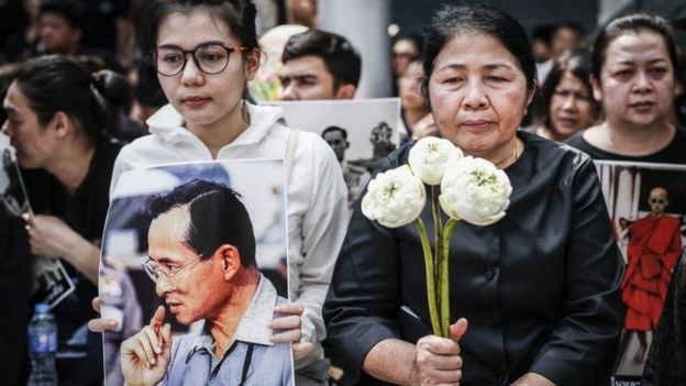 Thai mourners await the king's funeral procession
