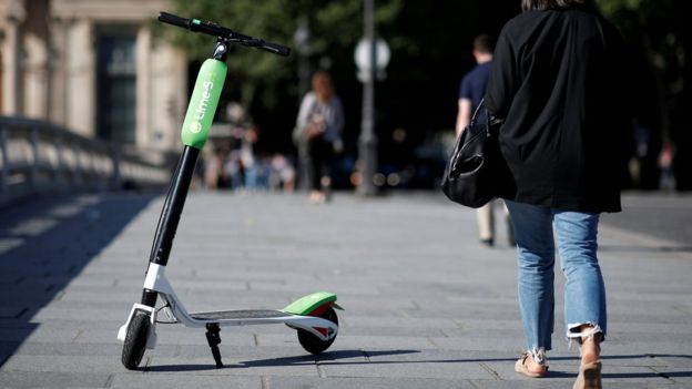 Imagem mostra patinete estacionado sobre calçada em Paris, enquanto pessoas caminham