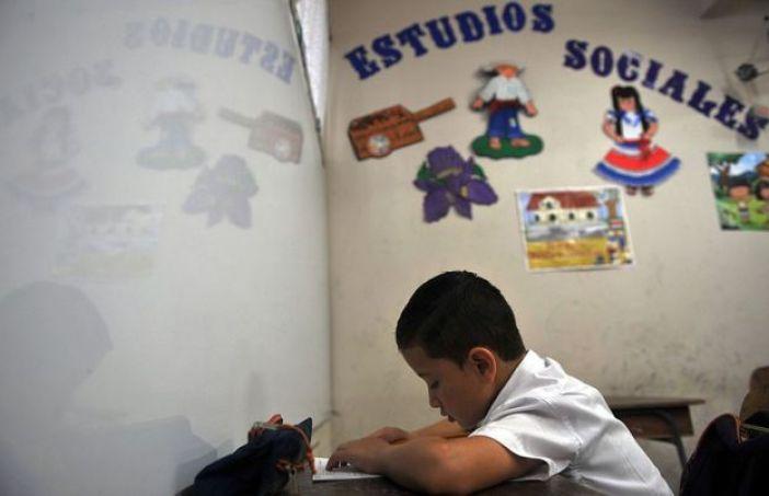 Niño tico estudiando.