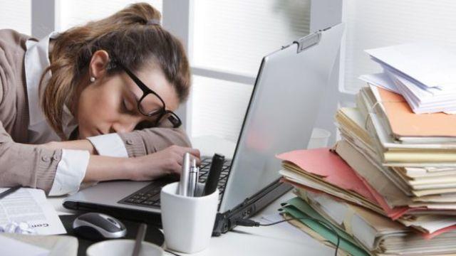 Mulher dorme sobre computador