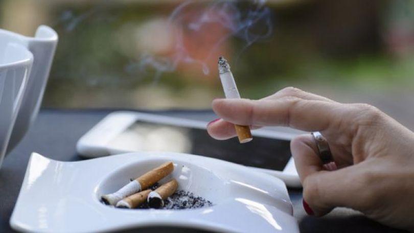Mão feminina segurando um cigarro aceso