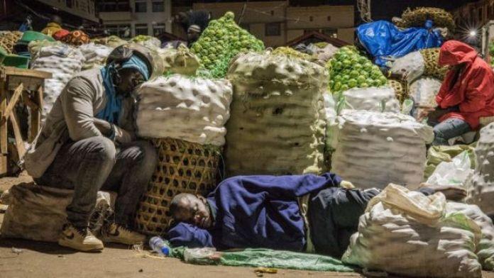 Les commerçants dorment à côté des articles à vendre sur un marché suite à une directive du président ougandais selon laquelle tous les vendeurs doivent dormir sur les marchés pendant 14 jours pour freiner la propagation du coronavirus COVID-19 sur le marché de Nakasero à Kampala, en Ouganda, le 7 avril 2020