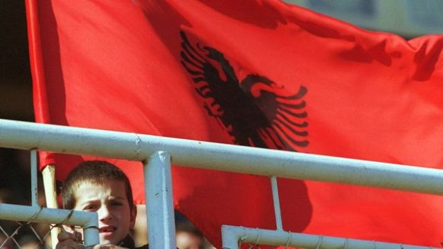 A young boy holds an Albanian flag October 21, 2000 as he watches a pre-election rally for the Democratic League of Kosovo
