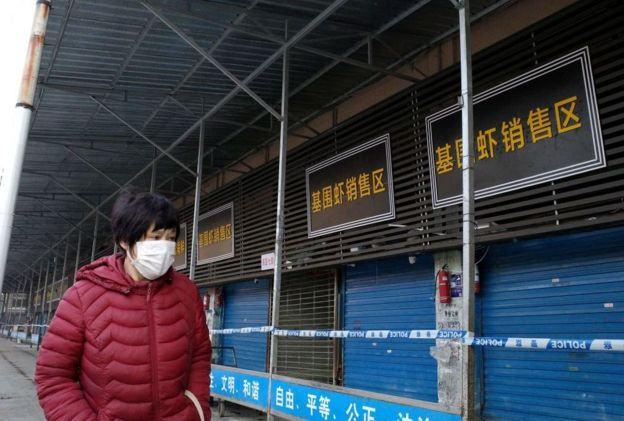 A woman walks in front of the closed Huanan wholesale seafood market in the Chinese city of Wuhan, Hubei province