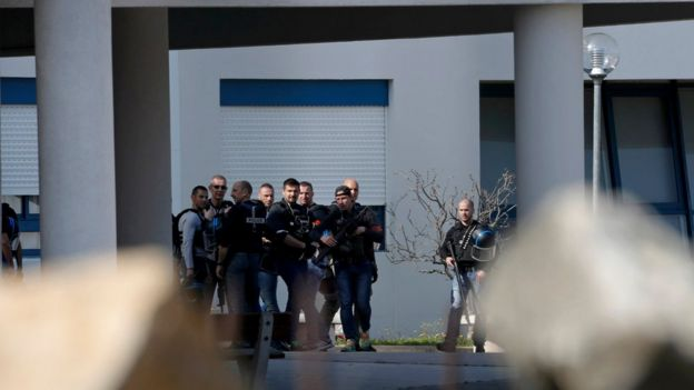 A group of armed police inside the Tocqueville high school after a shooting has taken place