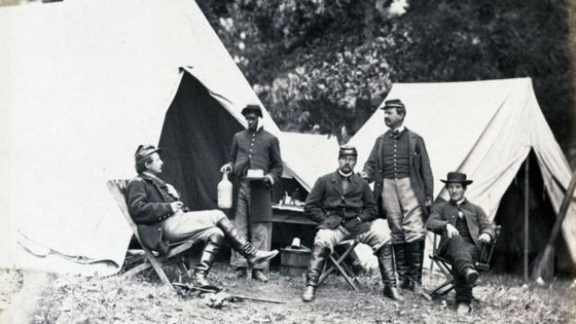 A black orderly serves drinks to Union officers during the Civil War