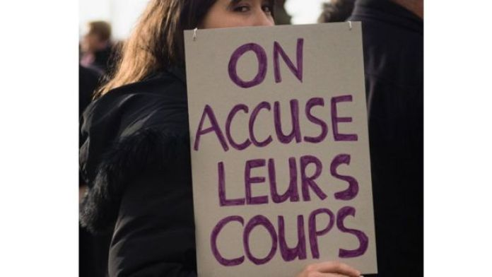 """Une militante contre les violence faites aux femmes tenant un pancarte avec linscription """" on accuse leurs coups"""""""
