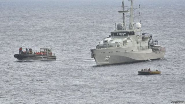 An Australian navy vessel and smaller boats
