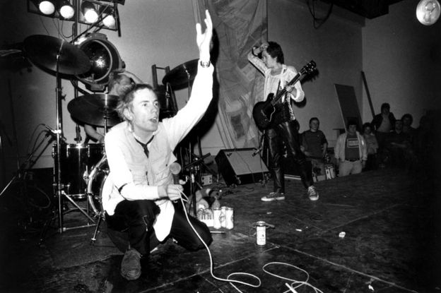 8th December 1976: The Sex Pistols: Johnny Rotten (John Lydon), Paul Cook (drums) and Steve Jones (guitar) performing on stage at Leeds Polytechnic, UK.