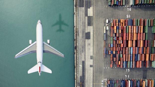 Avión volando junto a un carguero