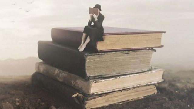 Mulher sentada em pilha de livros gigantes