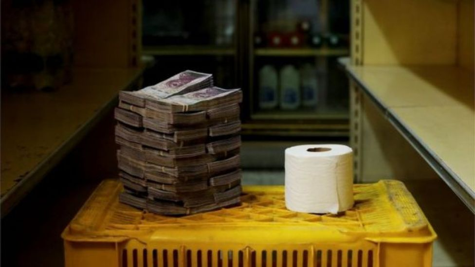 Pilha de notas de bolívares ao lado de rolo de papel higiênico