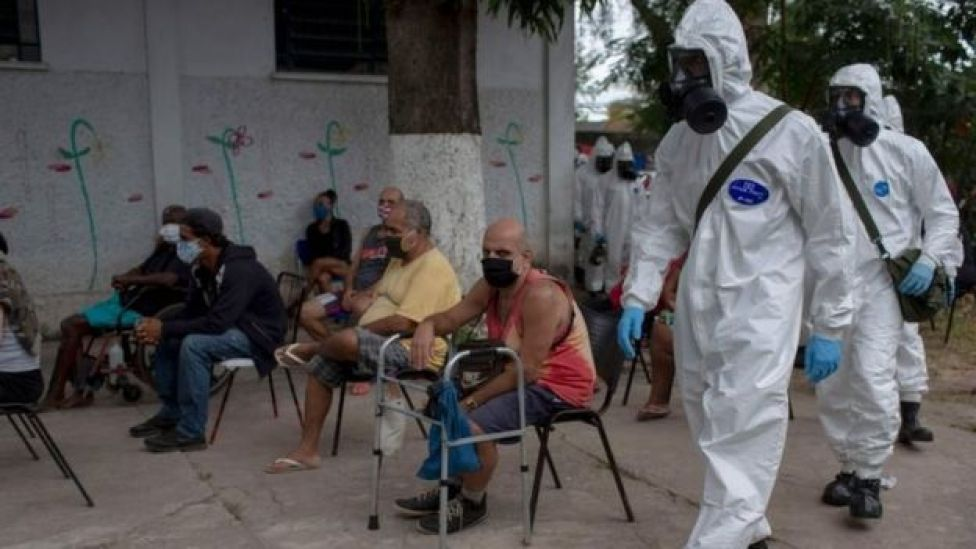 Brazilian soldiers in protective suits prepare to disinfect a public shelter in Rio de Janeiro. Photo: May 2020