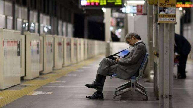 Homem com roupa formal dorm em estação de metrô
