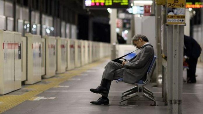 Empresario japonés dormido en una estación