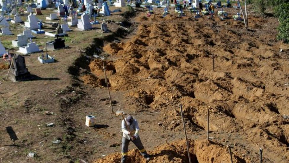 Homem abre covas onde foram enterrados os corpos de mortos em matança