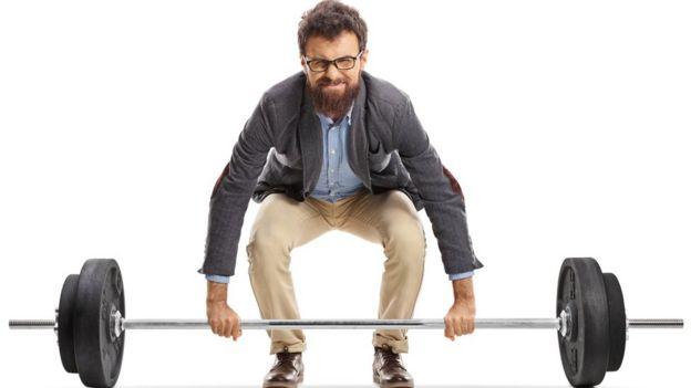 Hombre con ropa casual levantando una barra de peso libre.