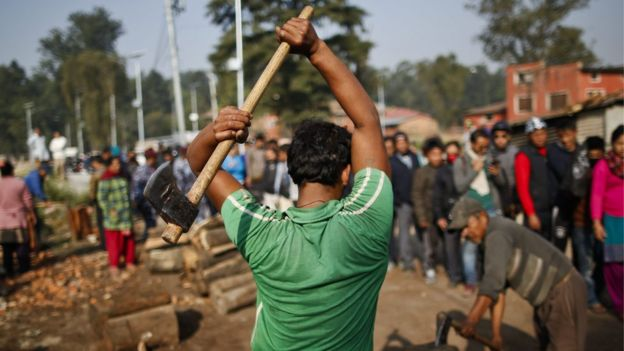 A Nepalese worker chops firewood sold by the government in Kathmandu, Nepal, 15 November 2015.