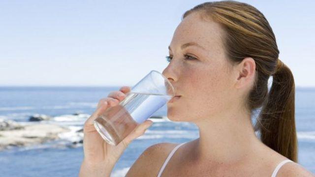 Mulher bebe água de copo com o mar ao fundo.