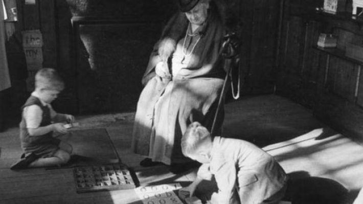 María Montessori con niños en el suelo.