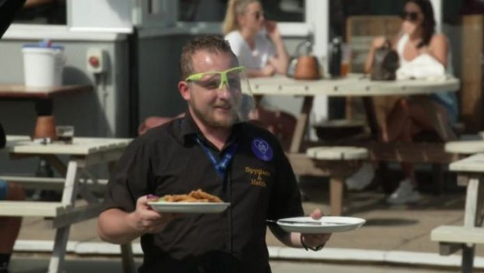 A waiter wearing personal protective equipment