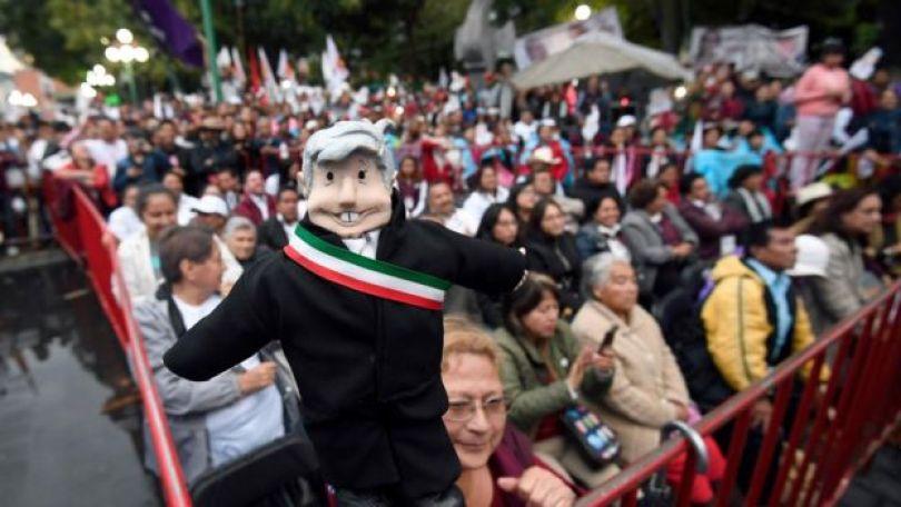 Boneco representando López Obrador, segurado por uma apoiadora do candidato em um comício no México