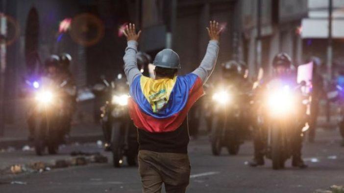 Hombre con una bandera de Ecuador frente a policías