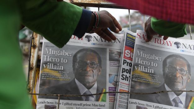 A man buys a daily newspaper at a stand on the streets of Nairobi following Robert Mugabe's death