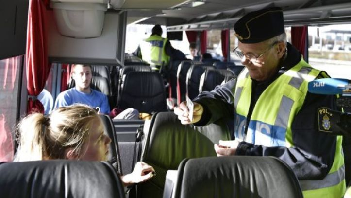 A police officer checks the documents a a passenger inside a bus at Lernacken on the Swedish side of the Oresund strait on 12 November 2015.