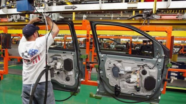 Hombre con una bandera de EE.UU. en la espalda trabajando en una fábrica de autos.