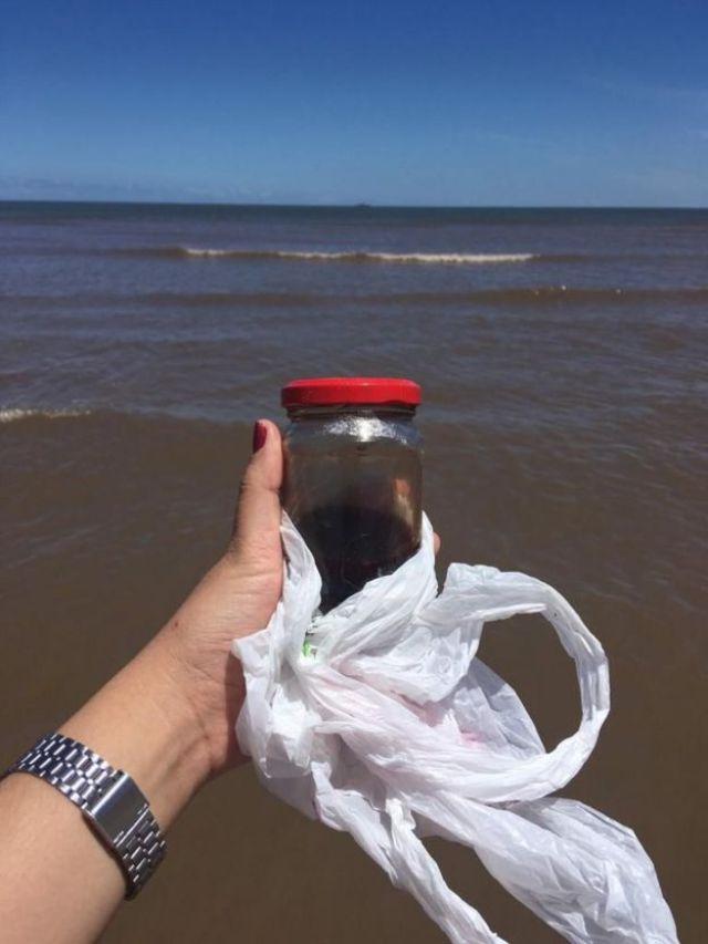 Imagem mostra mão de mulher segurando pote de vidro repleto de sangue, com imagem do mar ao fundo
