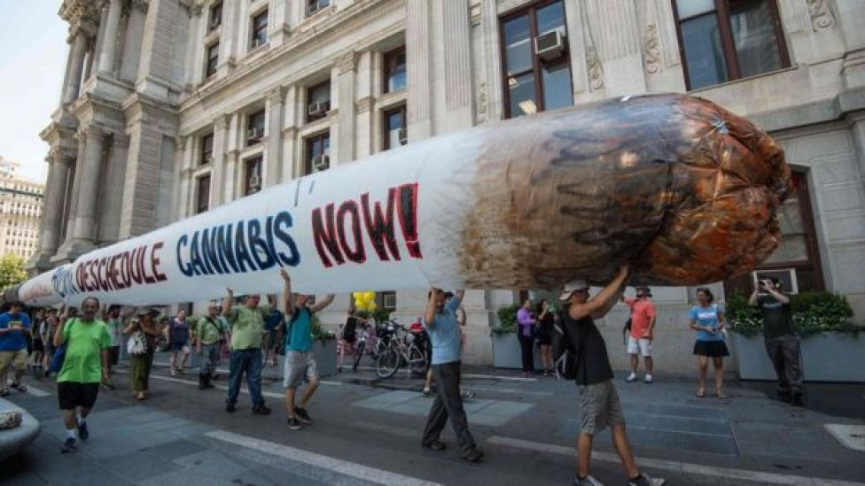 Supporters of former US Democratic presidential candidate Bernie Sanders hold a giant inflatable joint calling for the legalization of marijuana during a rally at City Hall in Philadelphia on July 25, 2016