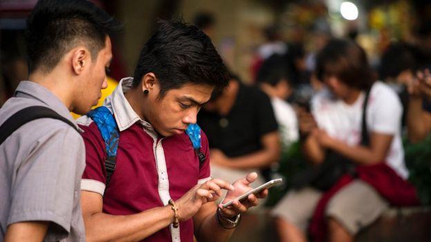 Dos jóvenes con el celular.