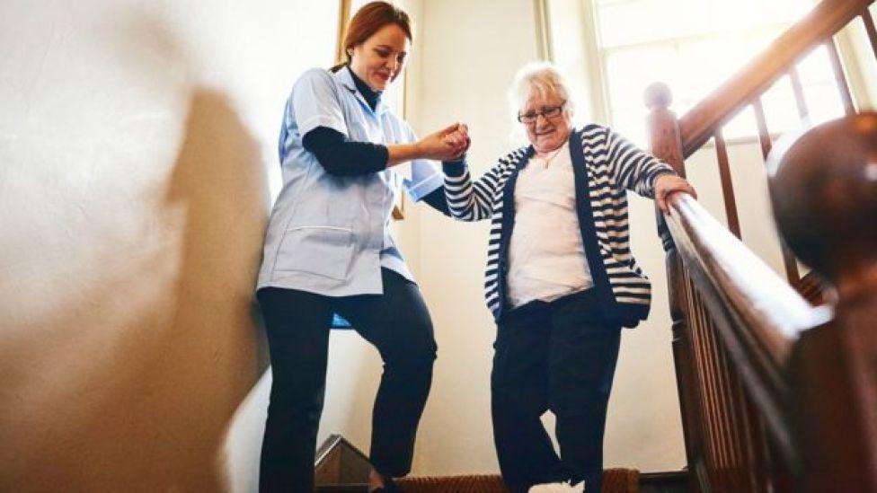 Mujer ayudando a anciana bajar escaleras