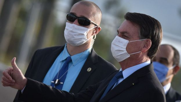 Wearing a protective face mask, Brazil's president Jair Bolsonaro arrives for the National Flag Raising ceremony in front of Alvorada Palace amid the Coronavirus (COVID-19) pandemic, in Brasilia, Brazil, on Tuesday, June 9, 2020