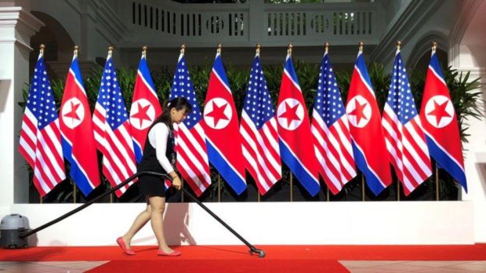Mulher aspira tapete vermelho onde Trump e Kim apertaram as mãos