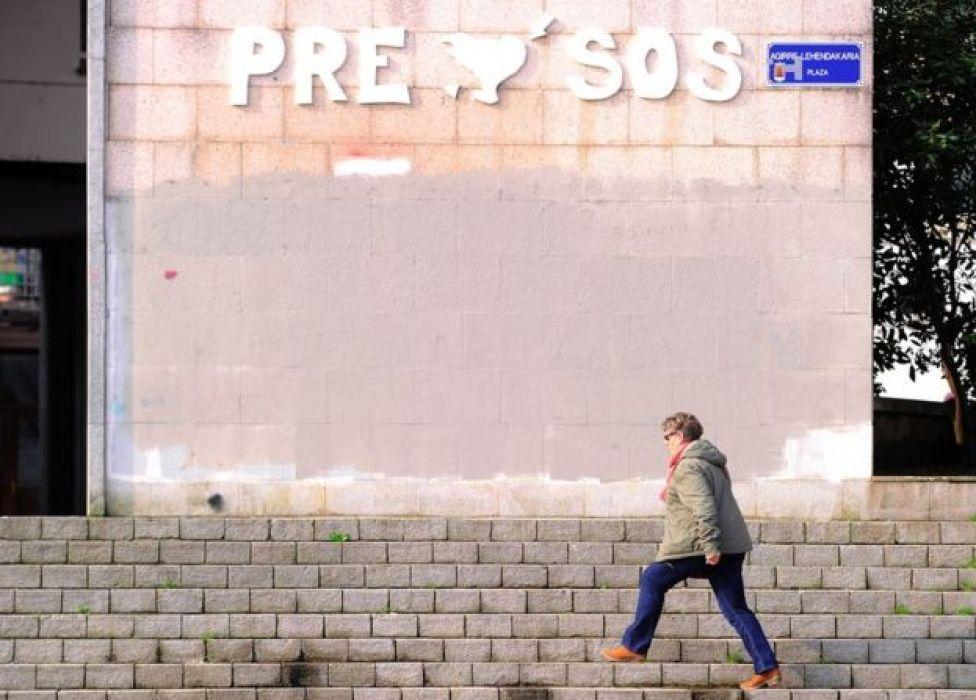 Mujer camina en Rentería, en la Comunidad Autónoma del País Vasco, España, el 8 de abril, ante una pared que reivindica el acercamiento de los presos de ETA a las cárceles del País Vasco.