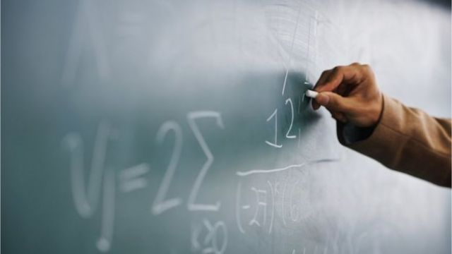 Homem escreve números em quadro negro