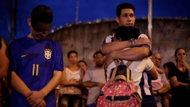 Estudantes e adultos se abraçam e olham consternados para entorno da escola Raul Brasil