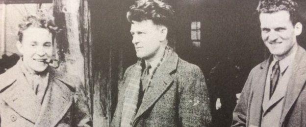 El entrenador y jugador del equipo, George Sinfield (centro), a su regreso al Reino Unido.